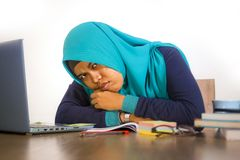 Young stressed and overwhelmed Muslim student woman in Islam hijab head scarf studying tired feeling overworked working with stock photo