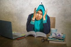 Young stressed and overwhelmed Muslim student woman in Islam hijab head scarf studying tired feeling overworked working with. Laptop computer and University stock photography