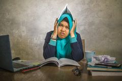 Young stressed and overwhelmed Muslim student woman in Islam hijab head scarf studying tired feeling overworked working with. Laptop computer and University stock image