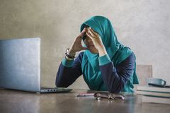 Young stressed and overwhelmed Muslim student woman in Islam hijab head scarf studying tired feeling overworked working with royalty free stock photography