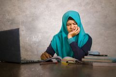 Young stressed and overwhelmed Muslim student woman in Islam hijab head scarf studying tired feeling overworked working with. Laptop computer and University royalty free stock photography