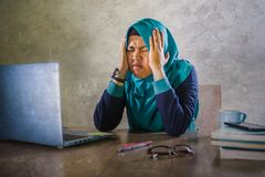 Young stressed and overwhelmed Muslim student woman in Islam hijab head scarf studying tired feeling overworked working with. Laptop computer and University stock images
