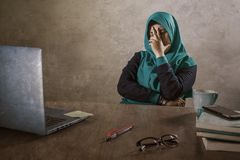 Young stressed and overwhelmed Muslim student woman in Islam hijab head scarf studying tired feeling overworked working with. Laptop computer and University royalty free stock image