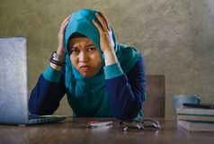 Young stressed and overwhelmed Muslim student woman in Islam hijab head scarf studying tired feeling overworked working with stock photos