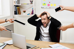 Young stressed overworked businessman in modern office Stock Photos
