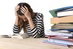 Young stressed student girl studying and preparing MBA test exam in stress tired and overwhelmed. Young stressed student girl studying pile of books on library stock photo