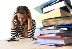 Young stressed student girl studying and preparing MBA test exam in stress tired and overwhelmed. Young stressed student girl studying pile of books on library Stock Image