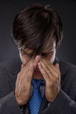 Young stressed and tired businessman. On gray Royalty Free Stock Photos