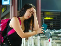 Young stressed and worried Asian Korean woman at airport tired and sad missing flight or suffering delay on holidays travel in. Young stressed and worried Asian royalty free stock images