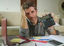 Young stressed and worried man at home living room using calculator and laptop doing domestic accounting paperwork feeling stock photography