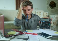 Young stressed and worried man at home living room using calculator and laptop doing domestic accounting paperwork feeling stock photo