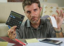 Young stressed and worried man at home living room using calculator and laptop doing domestic accounting paperwork feeling. Overwhelmed on money tax expenses royalty free stock photos