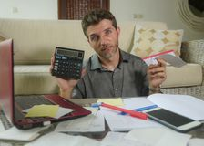 Young stressed and worried man at home living room using calculator and laptop doing domestic accounting paperwork feeling royalty free stock photography