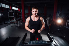 Young strong big man fitness model in the gym running on the treadmill with water bottle. Stock Photos
