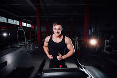 Young strong big man fitness model in the gym running on the treadmill with water bottle. Royalty Free Stock Photo
