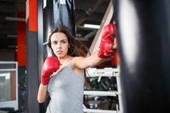 A young and strong girl beats a punching bag. A European young and strong girl is hitting a boxer`s pear in red pens. Inside stock image