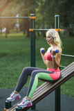 Young strong girl do exercises during street workout. Concept: sport, healthy lifestyle. Young strong girl do exercises during street workout Royalty Free Stock Images