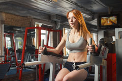 Young strong girl do leg lift for abs in gym Royalty Free Stock Photo