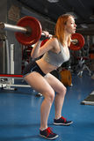 Young strong girl do squats with a barbell Royalty Free Stock Photography