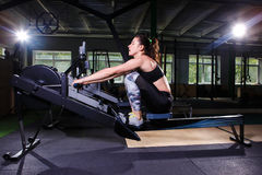 Young strong girl doing an exercise on a rowing machine. For training cardio arms, back. Sporting concepts Royalty Free Stock Images