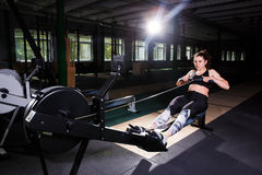 Young strong girl doing an exercise on a rowing machine. For training cardio arms, back. Sporting concepts Stock Photo