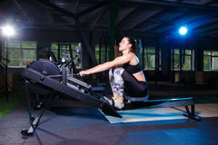 Young strong girl doing an exercise on a rowing machine. For training cardio arms, back. Sporting concepts Stock Image