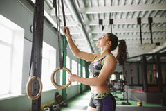 Young strong girl doing an exercise on a rowing machine. For training cardio arms, back. Sporting concepts Stock Photos