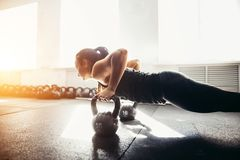 Woman doing push-ups exercises on kettlebells. Cross fit training. Young strong girl doing push-ups on kettlebells. focus on kettlebells royalty free stock photo