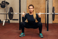 Young strong girl in the gym doing squat royalty free stock images
