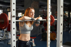 Young strong girl rest after squats with a barbell stock photography