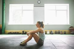 Young and strong girl with a smile doing exercises for the muscles of the stomach, press on the floor in the spore Royalty Free Stock Images