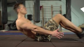 Young Strong Male Athlete Training Abdominal and Core Muscles