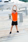 Young strong male jogger working out outdoors in summer sunny day. Full length portrait of an athletic man dressed in orange t-shirt with copy space for your Stock Images