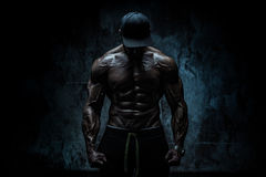 Strong man. Young strong man bodybuilder in cap on stone wall background. Dramatic dark contrast colors stock photo