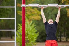 Young strong man does pull-ups on a horizontal bar on a sports ground in the summer in the city. royalty free stock image