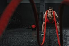 Young strong man doing battle ropes exercise at the crossfit gym royalty free stock image