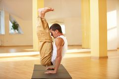 A young strong man doing handstanding yoga exercises - Urdhva Brahmachariasana in yoga studio Royalty Free Stock Photography