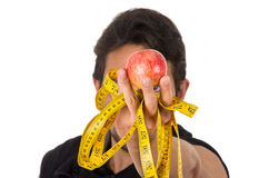 Young strong man holding red apple and measuring Royalty Free Stock Photos
