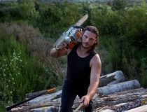 Lumberjack with chainsaw on logs. Young strong man lumberjack carrying chainsaw on shoulderand climbing on pile of logs royalty free stock image