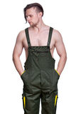 Young strong man with a naked torso in a working uniform stuck h royalty free stock photos