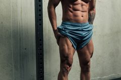 Young strong man posing and flexing his quadriceps legs muscles stock images