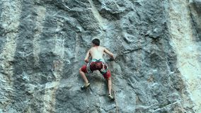 Young strong man rock climber carefully climbing on a cliff, searching, reaching and gripping hold.