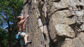 Young strong man rockclimber climbing on a granite cliff, reaching and gripping hold.
