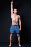 Young strong man in shorts doing kettlebell military press with. One hand. Fitness model trains in a studio on a dark gray background Royalty Free Stock Images
