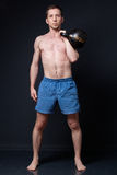 Young strong man in shorts fulfill kettlebell on his chest Stock Photography