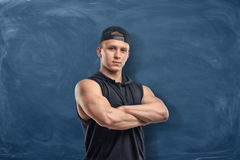 Young strong man standing in front of an empty blackboard with his arms across. A young strong man standing in front of an empty blackboard with his arms across royalty free stock image