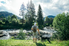 Young strong man stays near mountains river with dog and looking for the view. Young strong man with backpack stays near mountains river with dog and looking for Stock Image