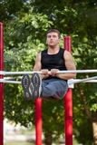 Young strong man swings the press on a horizontal bar on a sports ground in the summer in the city. Royalty Free Stock Photo