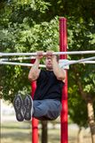 Young strong man swings the press on a horizontal bar on a sports ground in the summer in the city. Stock Images