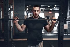 Man fitness. Young strong man during training in the gym royalty free stock photo